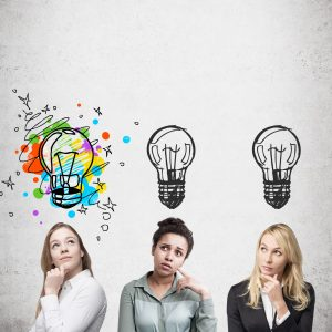 Three women are standing near concrete wall and thinking. Light bulb images are drawn above their heads. One is colorful. Concept of creativity. Mock up