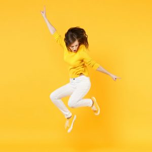Cheerful funny young woman in summer casual clothes jumping and spreading hands isolated on yellow orange wall background in studio. People sincere emotions, lifestyle concept. Mock up copy space