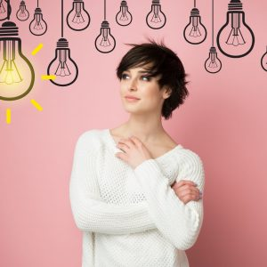 Beautiful young woman looking at light idea bulb above head, pink background with copyspace. Pretty brunette model and cartoon lamp. Girl thinks, solves a difficult problem and finds brilliant solution